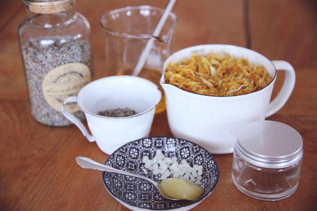 Zutaten für eine Lavendel Ringelblumen Salbe auf einem Tisch.